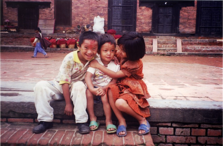 two-kids-hugging-a-smaller-kid-in-kathmandu-nepal